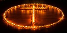Cross encircled by lit tealights
